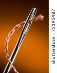 Metal needle and string. Very much a close up. Art background. - stock photo