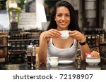Beautiful girl having coffee at cafe - stock photo