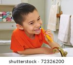 kid brushing teeth, looking in bathroom mirror - stock photo