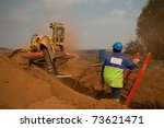 Construction worker watching a trencher machine digging and trench for a pipeline - stock photo