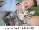 A man asleep on his sofa with a cute cat - stock photo