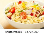 Rice like pasta orzo in a salad with basil, tomato, feta, and onion - stock photo