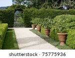 gravel garden walkway lined with potted plants, hedge with archway in the background, springtime - stock photo
