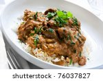 Beef stroganoff over white rice, garnished with parsley. - stock photo