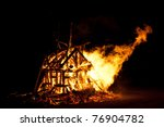 Burning Campfire or bonfire made from logs, shape of a burning house - stock photo