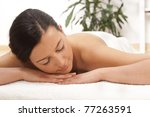 young woman lying on a massage table. relaxing with eyes closed - stock photo