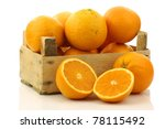 fresh oranges and two halves in a wooden box on a white background - stock photo