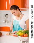 Young woman cutting vegetables in a kitchen - stock photo