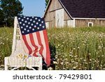 american flag draped over wicker chair in daisy field - stock photo