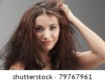 woman grabbing her tangled hair in frustration on grey background - stock photo
