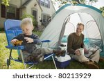 Father with laptop and son playing while camping in the front yard - stock photo