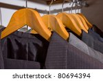 close up of suit men on wooden hangers - stock photo
