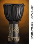A black djembe conga drum isolated against a yellow or gold spotlight background. - stock photo