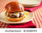Rare cheeseburger with caramelized onions and melted swiss cheese on large roll - stock photo