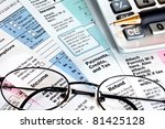 Tax forms with calculator, glasses and pen. - stock photo