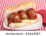 Meatballs covered with sauce and cheese on a bun - stock photo