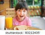 Wondered child girl has a healthy breakfast outdoors - stock photo