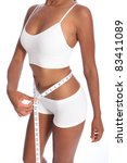 Healthy torso of young african american woman wearing white sports underwear, checking diet weight loss on waist with tape measure, standing against white background. - stock photo