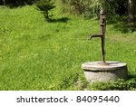 Water well at meadow. - stock photo