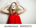 Cute little happy girl posing in a red dress. - stock photo