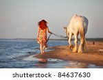 Woman with big white horses going along seashore - stock photo