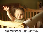 Baby girl waving hand and standing up in crib - stock photo