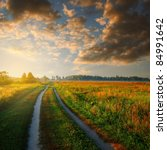 road in field and cloudy sky at sunrise time - stock photo