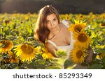 beautiful woman between sunflowers - stock photo
