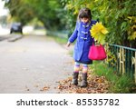 Funky little girl in blue coat walking down the street with bunch of leaves and pink bag - stock photo