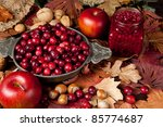 Thanksgiving still-life with cranberries, autumn leaves, apples and nuts - stock photo