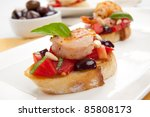 Closeup of delicious Olive - Tomato Bruschetta with garlic shrimp and pine nuts. - stock photo