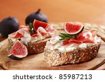 Sandwich with cream cheese, prosciutto, fig and rocket - stock photo