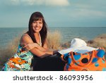 Beautiful young girl smiling. She sits on the background of the sea with their bags. - stock photo