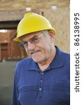 Man at a construction site/Mature construction worker/Man with hard hat working at a construction site - stock photo