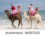 children riding camels on the beach by the sea - stock photo