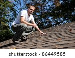 Horizontal shot of roofer on work repairing shingles - stock photo
