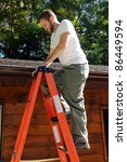 Man climbing ladder to roof for repairs - stock photo