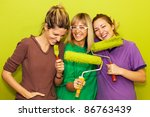 Young friends painting a room, smiling. - stock photo