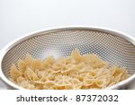Pasta bow in strainer - stock photo