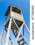 Wooden watchtower in prison camp over blue sky - stock photo