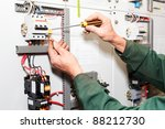 Electrician`s hands working with screwdriver in cables and wires. - stock photo