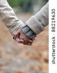 Closeup of couple holding hands while walking in park - stock photo