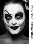 a scary female clown staring from the dark - stock photo