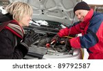 Woman getting a boost for her car - stock photo