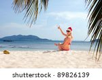 Young woman on the beach in santa's hat - stock photo