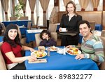 Happy family having breakfast at a restaurant - stock photo