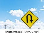 u-turn symbol and a beautiful blue sky - stock photo