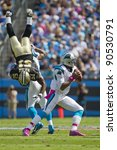 CHARLOTTE, NC - OCT 09, 2011:  Saints Linebacker, Jonathan Vilma, is flipped while Panthers Quaterback, Cam Newton, sets up to pass at Bank of America Stadium in Charlotte, NC on Oct 9, 2011. - stock photo