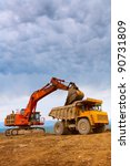 Excavator loading big heavy yellow truck - stock photo