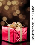 Red gift box with golden ribbon, glittery gold background - stock photo
